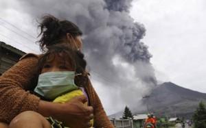 Seorang ibu mengendong anaknya menjauhi awan panas dari erupsi Gunung Sinabung, Sumut. (foto: metronews.com)