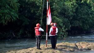 Petugas upacara komunitas Sungai Ciliwung mengibarkan bendera merah putih di tengah Sungai Ciliwung, Depok, Ahad, 17 Agustus 2014. Pengibaran bendera ini untuk memperingati hari Kemerdekaan Reuoblik Indonesia yang ke-69. TEMPO/Il