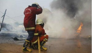 2 petugas pemadam kebakaran sedang berusaha memadamkan api saat terjadinya kebakaran di proyek Tol Cijago yang terjadi pada Selasa lalu.